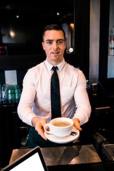 バーテンダーがバーでお客様にコーヒーを与える