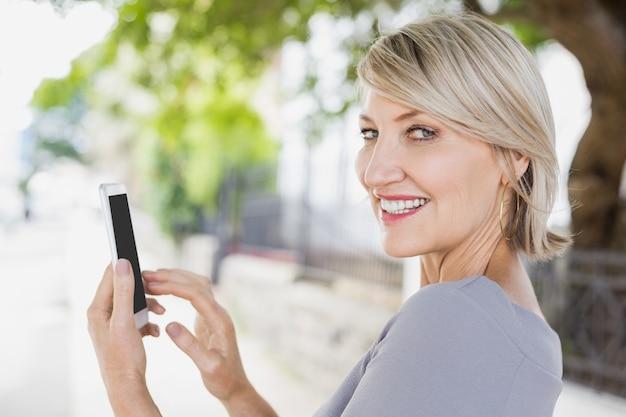 スマートフォンを使用して女性のクローズアップの肖像画