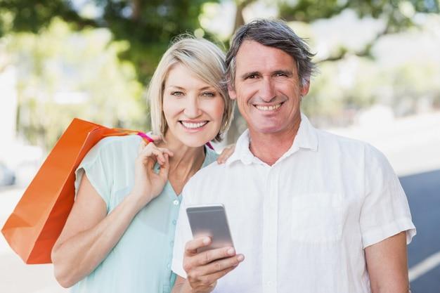 Портрет пары с мобильным телефоном и сумками