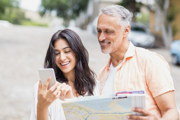 地図を押しながら携帯電話を使用してカップル