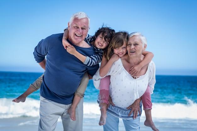 子供たちにおんぶを与える幸せな祖父母