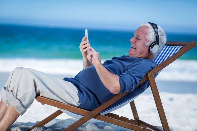 中年の男性がスマートフォンで音楽を聴くデッキチェアで休む