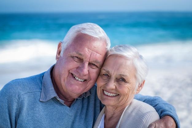 ビーチで抱きしめるかわいい成熟したカップル