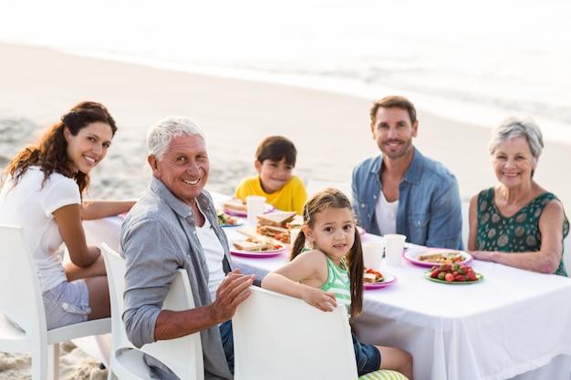 ビーチでピクニックを持つ幸せな家族