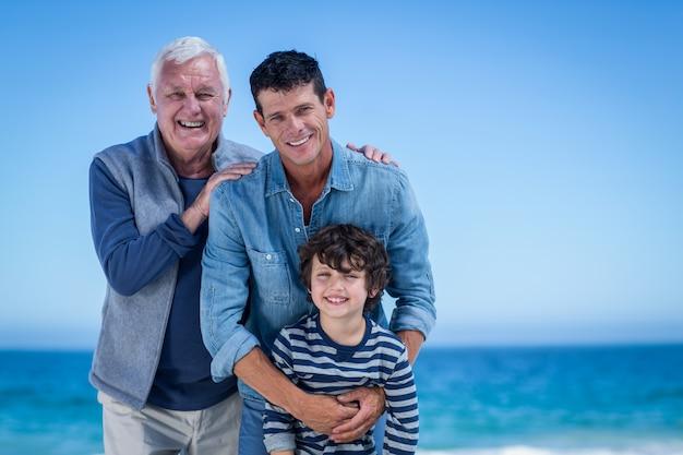 男性の家族がビーチでポーズ