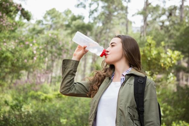 女性はバックパックで水を飲む