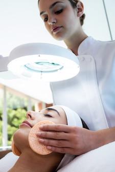Массажистка чистит женское лицо ватными тампонами