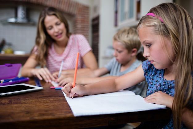Мать помогает детям с домашней работой