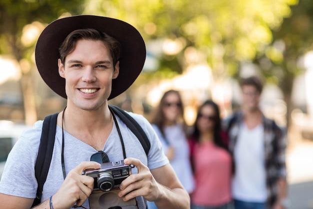 デジタルカメラを押しながらカメラに笑顔のヒップ男