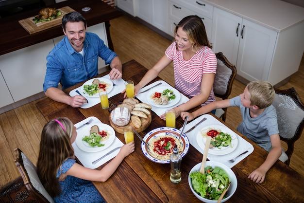 Счастливая семья разговаривает друг с другом во время еды на кухне