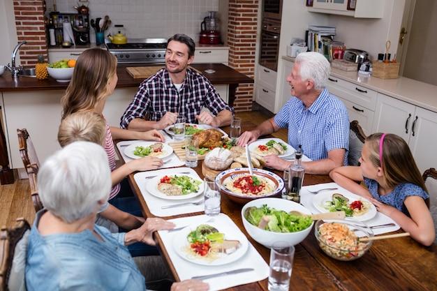 キッチンで食事をしながら話している多世代家族