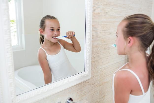 浴室で彼女の歯を磨く幸せな女の子