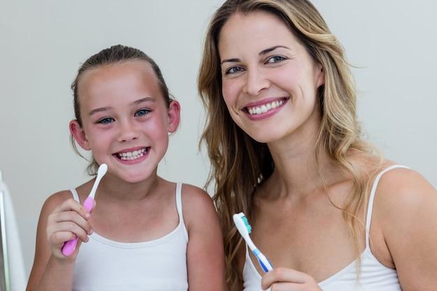 幸せな娘とバスルームで歯ブラシを保持している母の肖像画