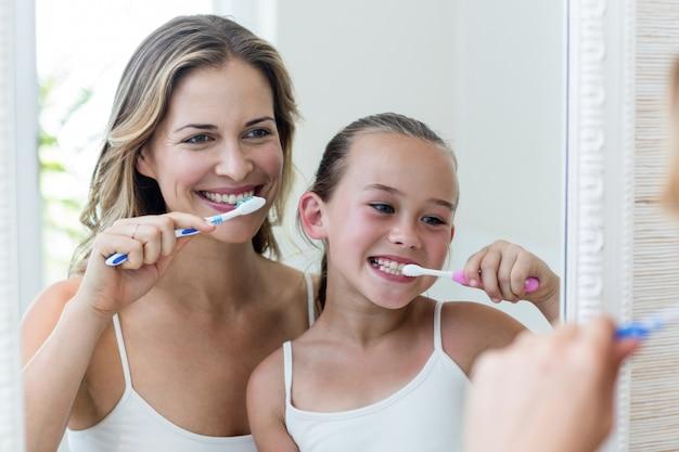 母と娘がトイレで歯を磨く