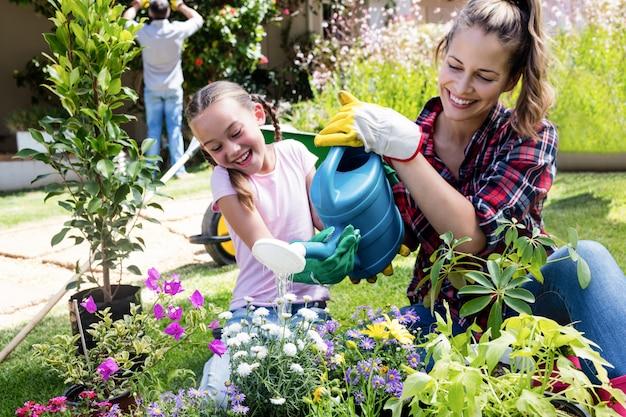 母と娘は庭の植物に水をまく