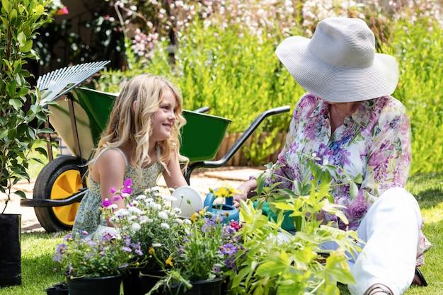 祖母と孫娘が庭の植物に水をまく