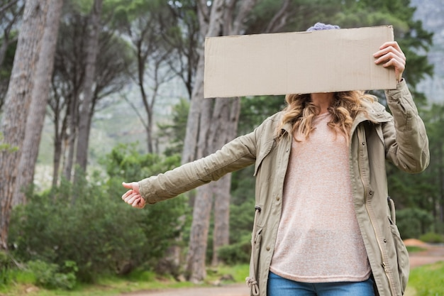 Автостопом женщина держит картон