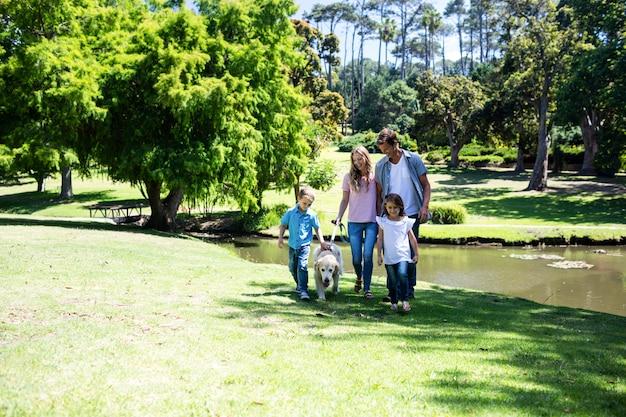 Семья гуляет в парке со своей собакой