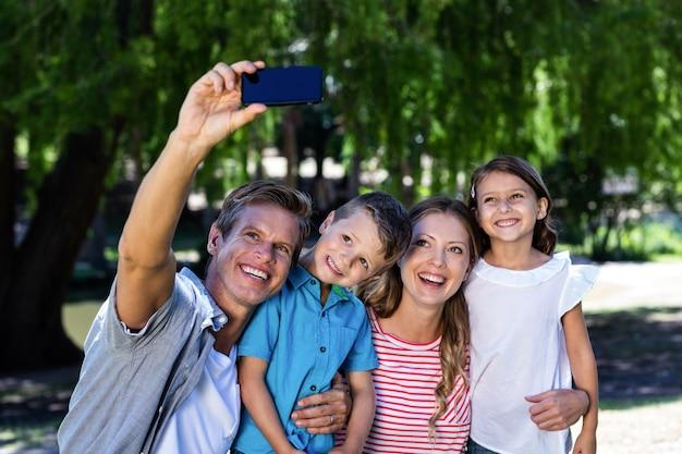 Счастливая семья, принимая селфи в парке