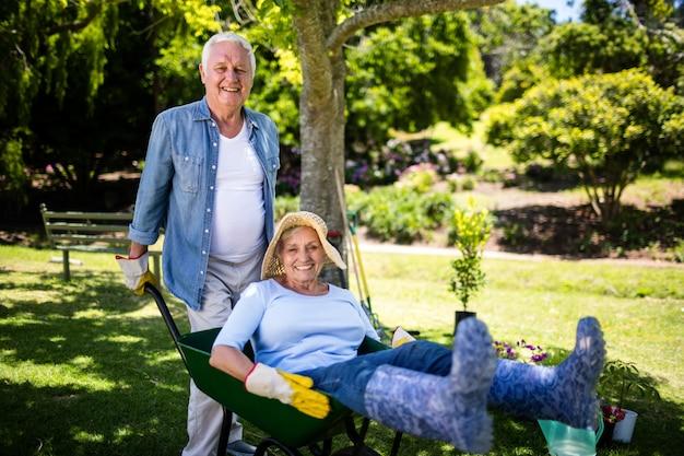 手押し車で遊ぶ年配のカップル