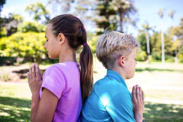 Братья и сестры молятся в парке