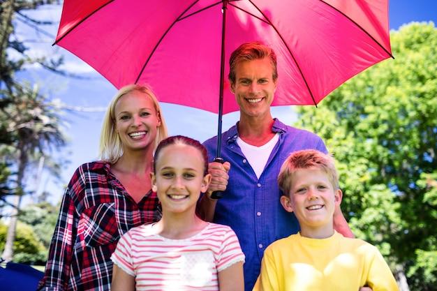Семья стоит под зонтиком