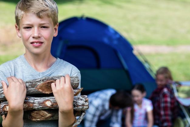Мальчик несет дрова возле палатки