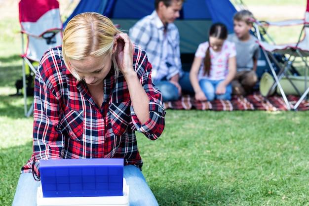 Женщина смотрит в прохладную коробку возле палатки
