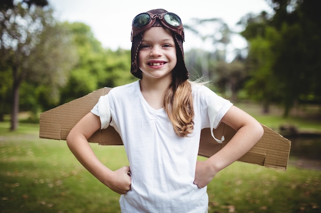 腰に手で公園に立っている幸せな女の子