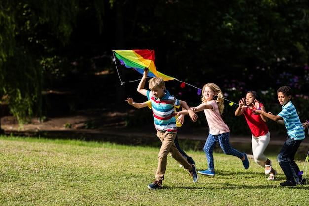 Счастливые дети играют с воздушным змеем