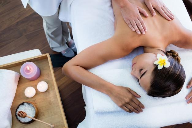 Массажистка дает массаж, чтобы расслабить женщину