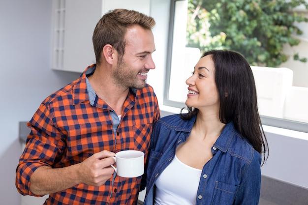 台所でお茶を持っているカップル