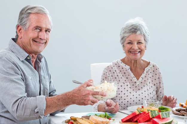 朝食を持っている老夫婦