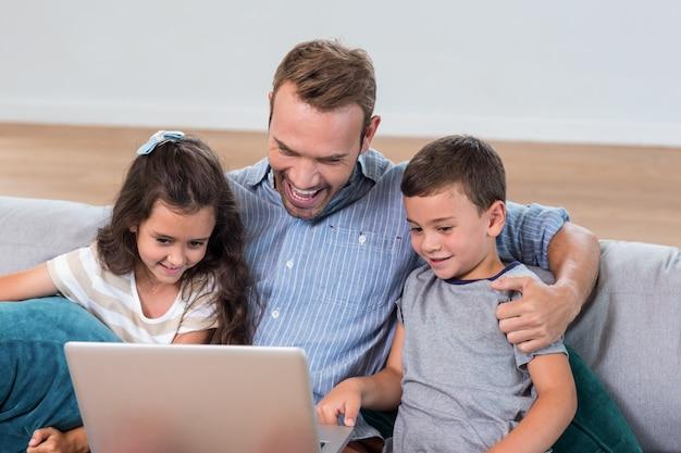 父は息子と娘と座っているとラップトップを使用して