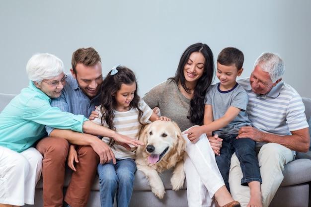 Семья сидит на диване с собакой