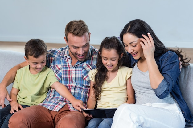 息子と娘と一緒に座って、デジタルタブレットを見て親