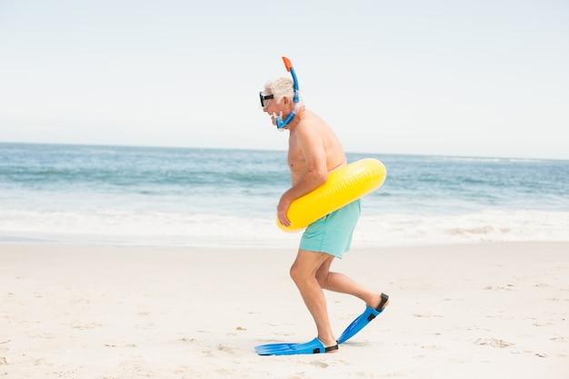 水泳リングとビーチで足ひれを持つ年配の男性