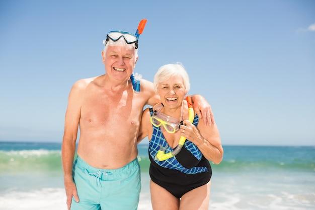 シュノーケルとダイビングゴーグルを着ている年配のカップル