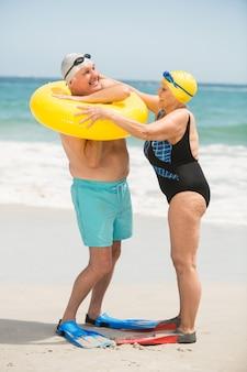 ビーチでの水泳リングと年配のカップル