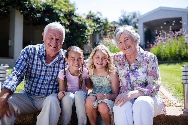 Бабушка и дедушка и внучки сидят в саду