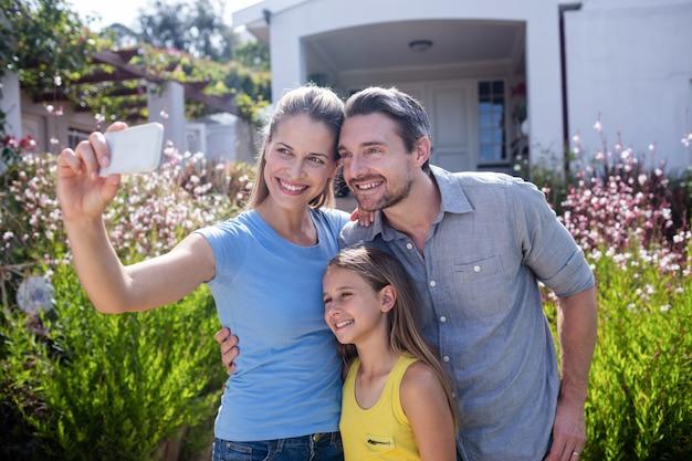 Родители и дочь, принимая селфи на мобильный телефон