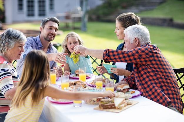 Счастливая семья обедает в саду
