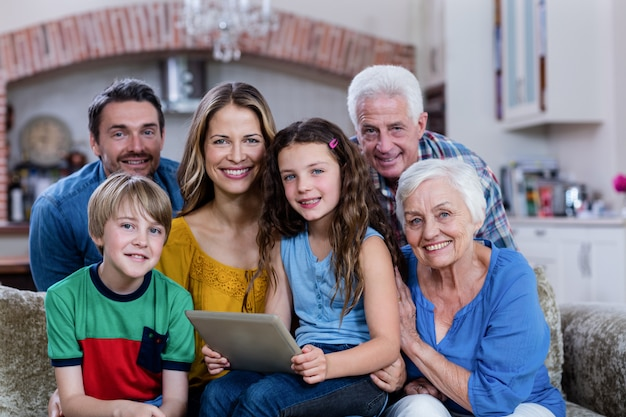 Портрет семьи нескольких поколений сидя на софе и используя цифровую таблетку