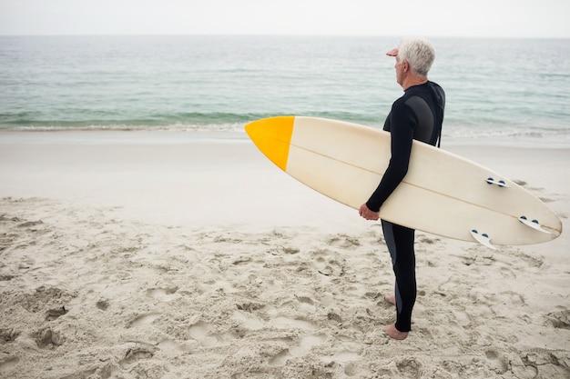 ビーチで目をシールドサーフボードを持つシニア男