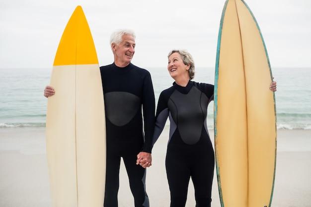 ビーチで手を握ってサーフボードと年配のカップル