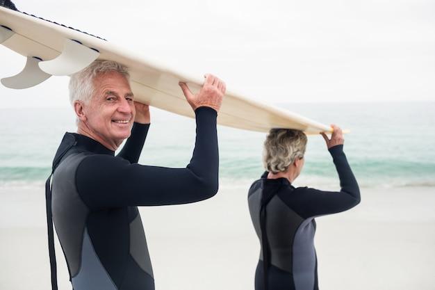 サーフボードを頭の上に運ぶウェットスーツの年配のカップル