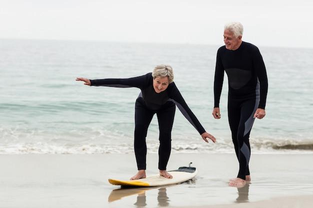 サーフィンする女性を教える年配の男性