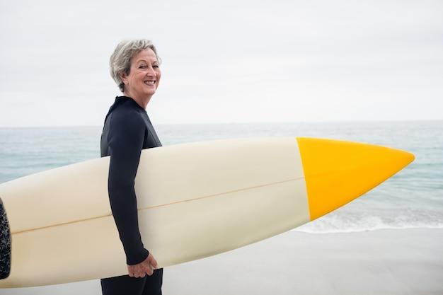 ビーチでサーフボードを保持しているウェットスーツの年配の女性