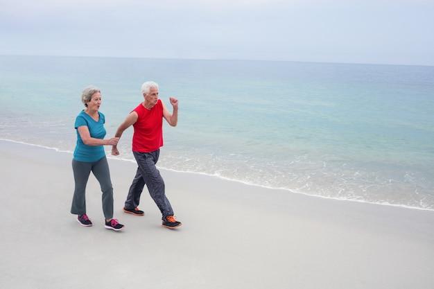 年配のカップルがビーチでジョギング