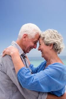 ビーチでの顔を受け入れる年配のカップル